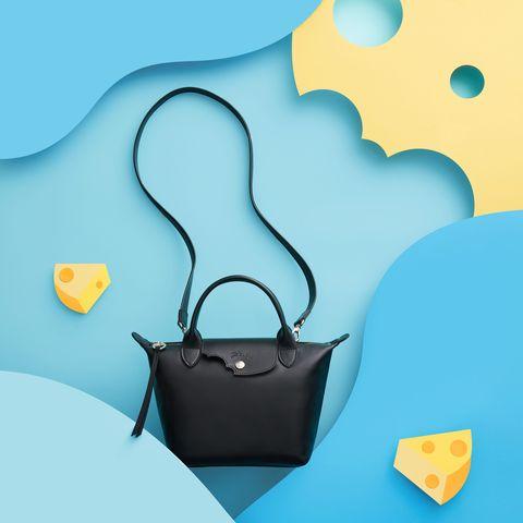 Longchamp以「美食家」作為靈感來源, 加入起司元素為黑色牛皮手袋增添一股俏皮風格,