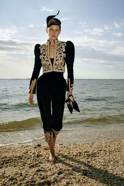 model in black and gold jacket and pants