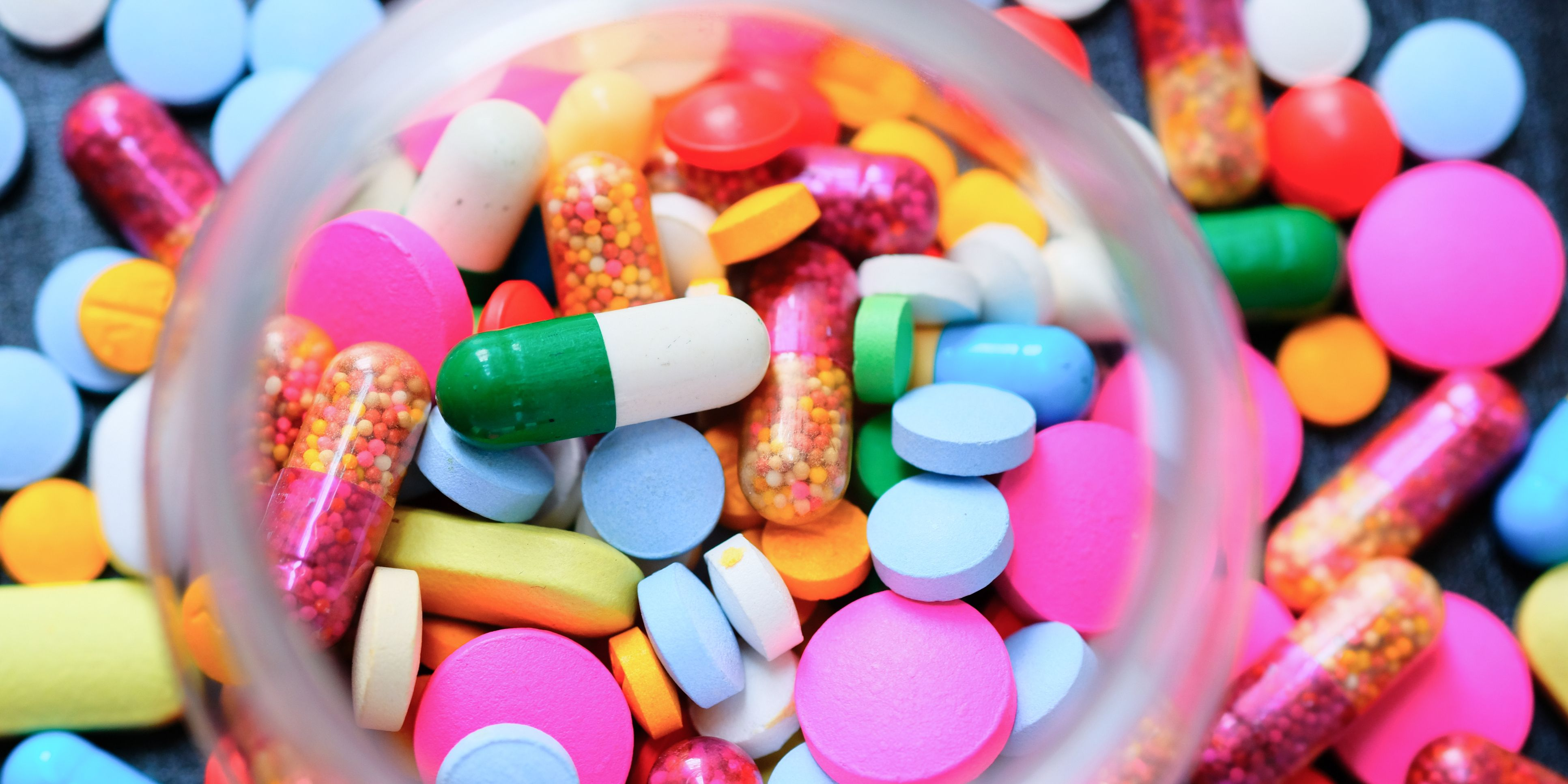Looking down on a open prescription bottles with assorted pills