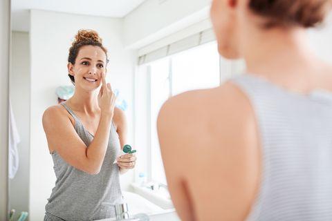 mujer joven hidratando su rostro con crema para evitar la sequedad en la piel