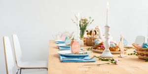 Decorated Easter table with field flowers in vase, burning candles, painted Easter eggs, homemade buns, paper-mache goose and wooden Easter bunny