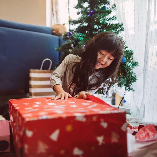 lovely little girl opening christmas presents at home joyfully