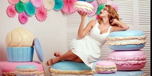 Lovely woman with huge marshmallow and cake sweets concept studio