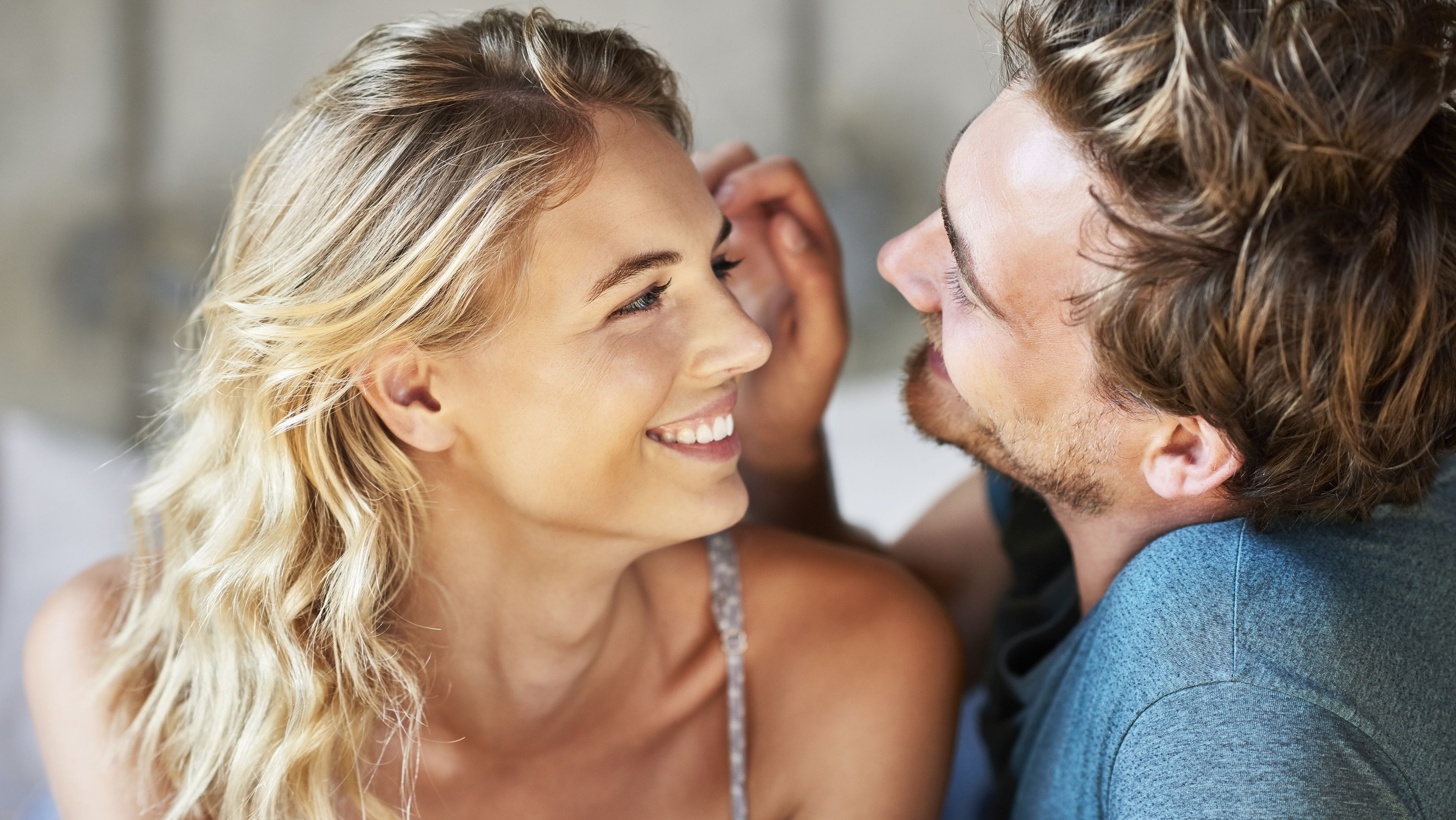 Loving man is playing with woman's hair at home