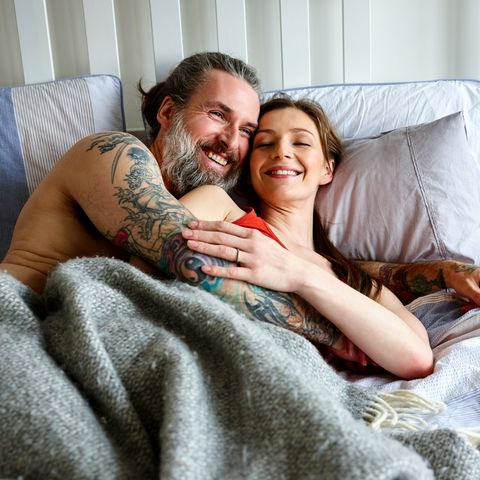 Loving pregnant couple embracing on bed at home