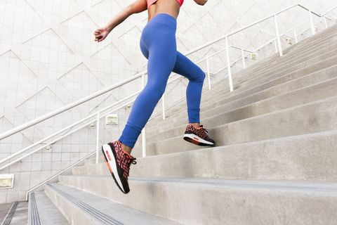 Low angle rear view of young woman, wearing sports clothing running up stairs