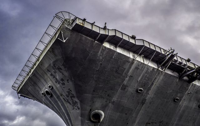low angle view of aircraft carrier against cloudy sky