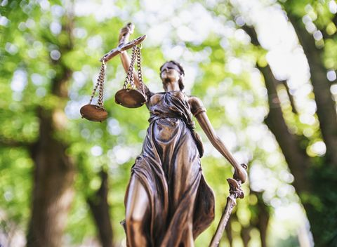 Low Angle View Of Lady Justice Against Trees