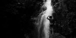 Low Angle View Of Naked Man Standing Against Waterfall