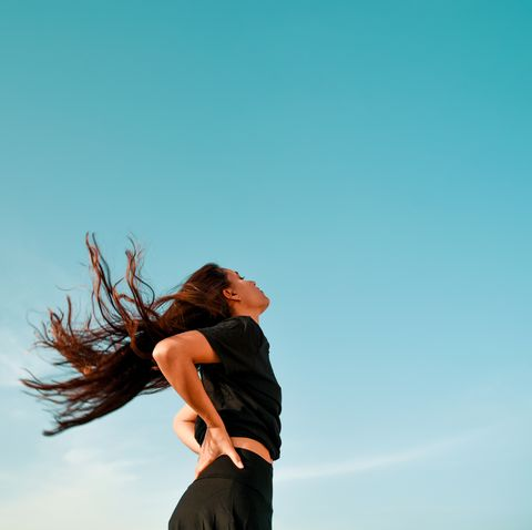 low angle view of woman with long hair standing against clear blue sky