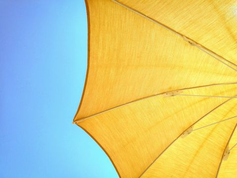 low angle view of yellow parasol against clear blue sky