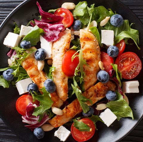 Low-calorie salad with blueberries, feta, chicken, nuts, tomatoes and lettuce close-up. horizontal top view