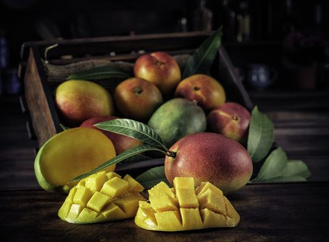 low key image close up of sliced ripe mangoes in rustic kitchen
