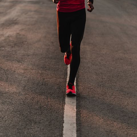 Low Section Of Athlete Running On Road