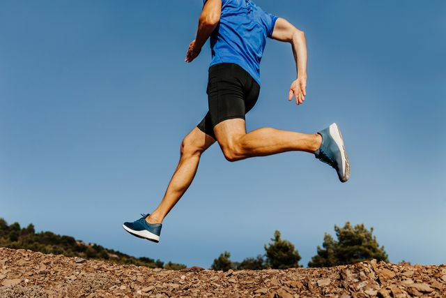low section of man running against clear blue sky