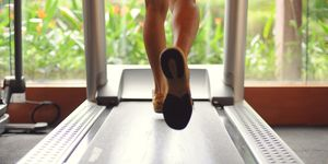 Low Section Of Man Running On Treadmill At Gym