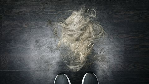 Low Section Of Man Standing By Hair On Floor