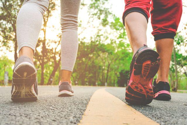 dos personas caminando por una carretera