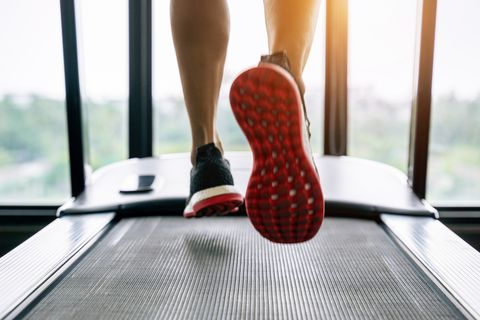 Low Section Of Person Exercising On Treadmill In Gym