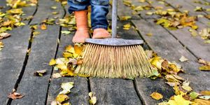 Person sweeping up autumn leaves on wooden floor outside