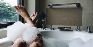 Low Section Of Woman Bathing In Bathtub