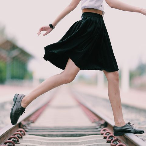 low section of woman crossing railroad track