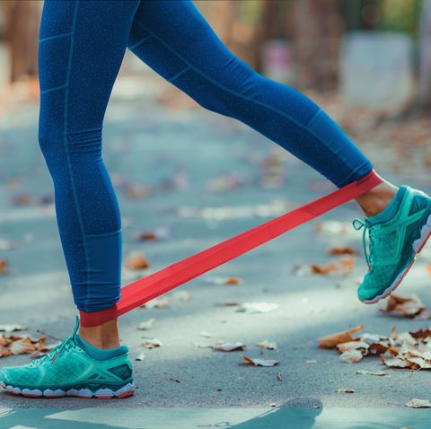low section of woman exercising with resistance band on road during autumn