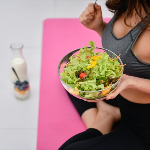 low section of woman having breakfast while sitting in yoga studio