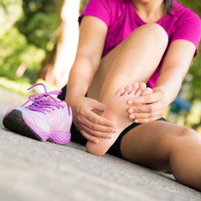 Low Section Of Woman Holding Foot In Pain While Sitting On Road