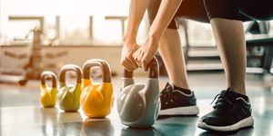 Low Section Of Woman Holding Kettlebell At Gym