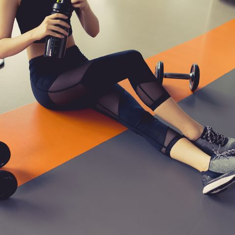 Low Section Of Woman Holding Water Bottle In Gym