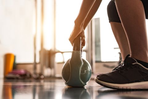 Low Section Of Woman Lifting Kettlebell At Gym