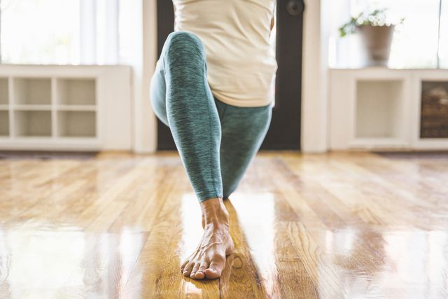 low section of woman practicing yoga on hardwood floor in gym