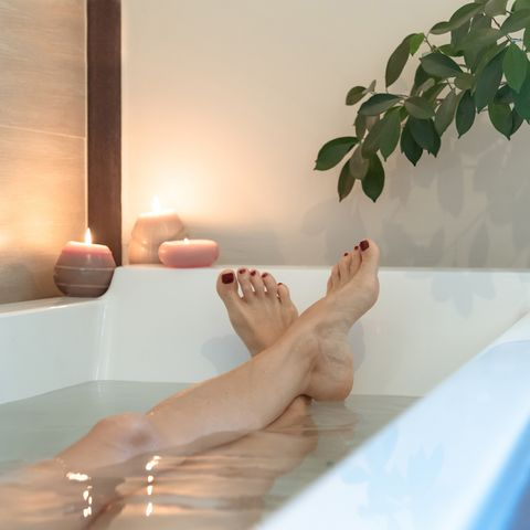 low section of woman relaxing in bathtub