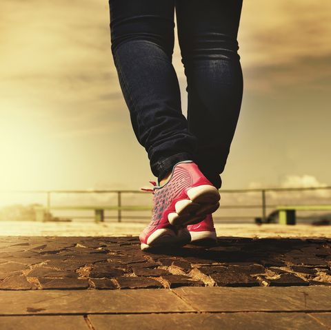 Low Section Of Woman Running On Footpath Against Cloudy Sky During Sunset