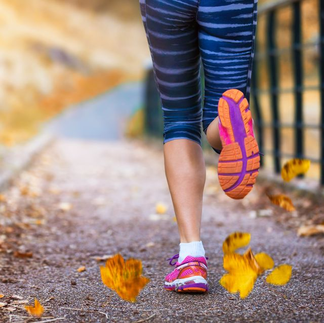 Low Section Of Woman Running On Footpath During Autumn