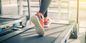 Low Section Of Woman Running On Treadmill In Gym