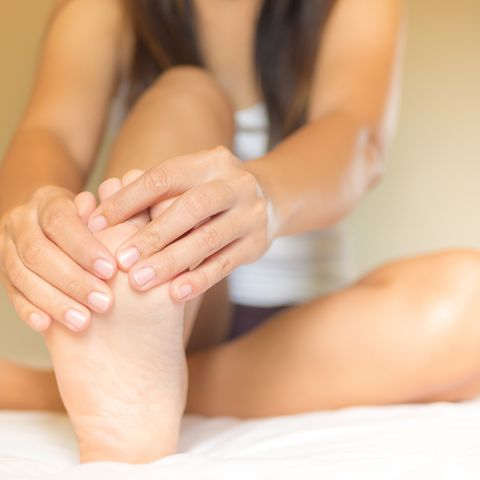 Low Section Of Woman Touching Foot In Pain While Relaxing On Bed