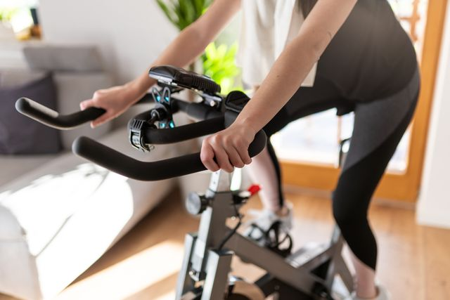 low section of woman training on exercise bike at home, spin workouts