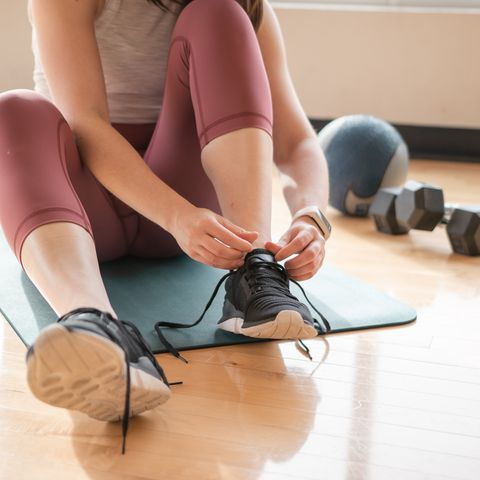 low section of woman tying shoelace at home
