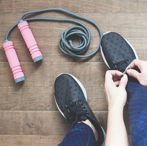 low section of woman tying shoelace by skipping rope on hardwood floor