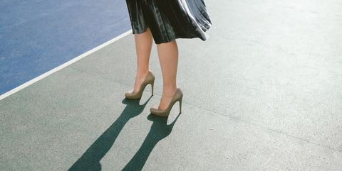 Low Section Of Woman Wearing High Heels While Standing On Street