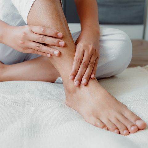 low section of woman with ankle pain sitting on bed