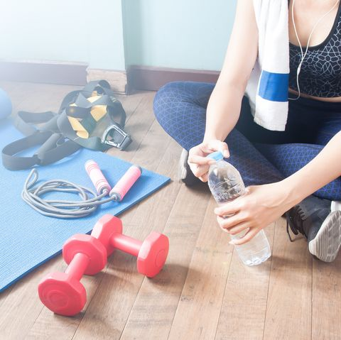 Low Section Of Woman With Water Bottle By Dumbbells On Hardwood Floor