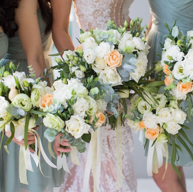 low section of women holding flower bouquets