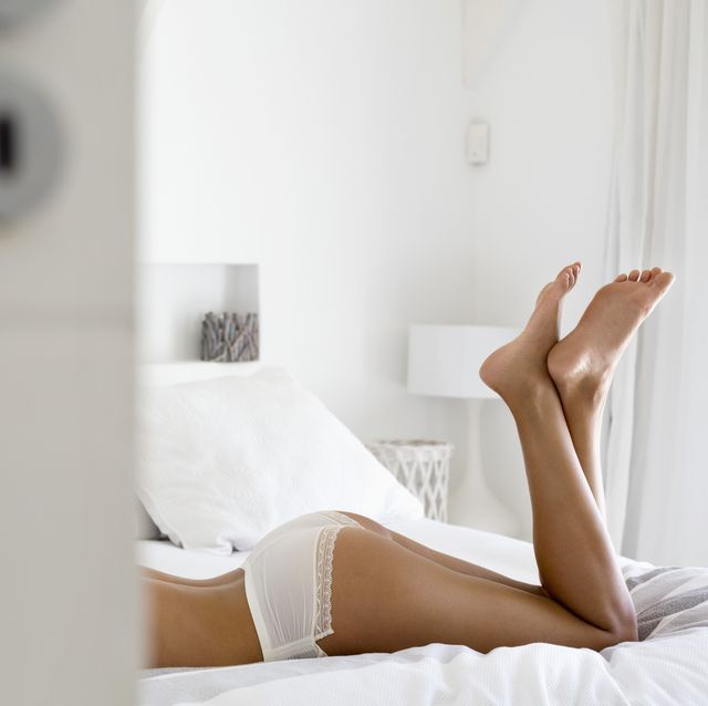 Low section view of a woman lying on the bed in lingerie