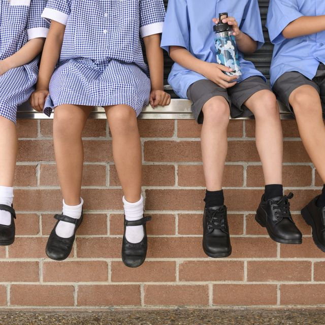low section view of five school children sitting on brick wall wearing school uniform