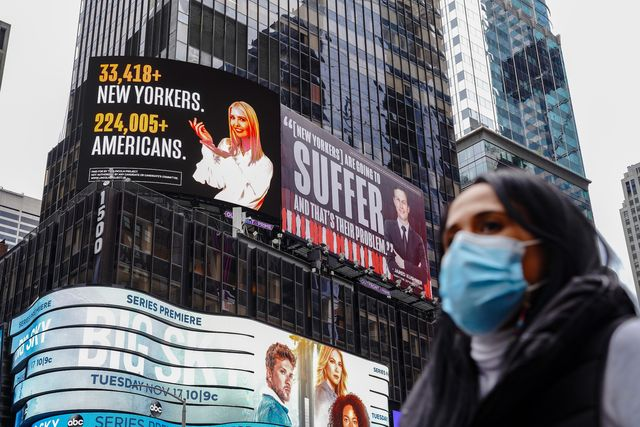 new york, united states   20201025 a woman wearing a face mask walks past a lincoln project billboard that depicts ivanka trump presenting the number of new yorkers and americans who have died of covid 19 and jared kushner next to a vanity fair quote photo by john nacionsopa imageslightrocket via getty images