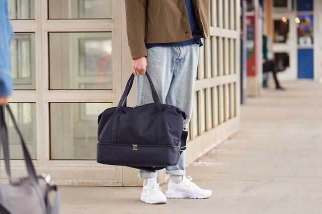 lo and sons man holding weekender bag