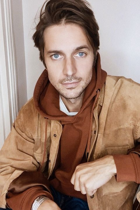 Лукас Браво в худи цвета ржавчины и коричневой замшевой куртке смотрит в камеру
